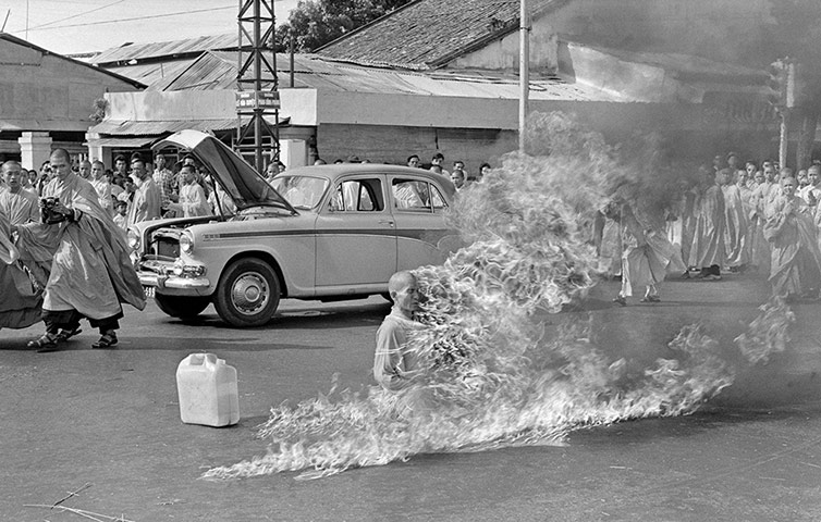 In the first of a series of fiery suicides by monks, Thich Quang Duc burns himself to death on a Saigon street to protest persecution of Buddhists by the South Vietnamese government on 11 June 1963. The photograph aroused worldwide outrage and hastened the end of the Diem government. With the photo on his Oval Office desk, President Kennedy reportedly remarked to his ambassador, 'We're going to have to do something about that regime' ~ Photograph: Malcom Browne/AP