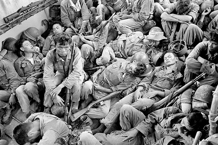 Exhausted South Vietnamese soldiers sleep on a US Navy troop carrier taking them back to the provincial capital of Ca Mau in August 1962. The infantry unit had been on a four-day operation against the Viet Cong in swamplands at the southern tip of the country ~ Photograph: Horst Faas/AP