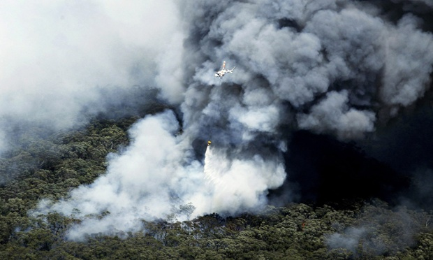 An aerial image shows a fire-fighting helicopter over a smoke cloud, after a devastating bushfire passed through at Yellow Rock in the Blue Mountains, west of Sydney, Australia.