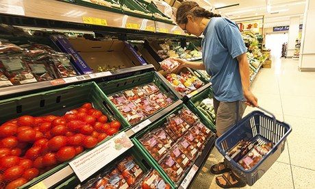 Woman shopping in Tesco supermarket, UK