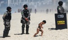 A boy walks past military police standing guard outside the seafront Windsor Barra hotel in Rio de Janeiro, Brazil.