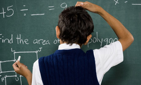 Rear view of boy at chalkboard doing math formulas and scratching head