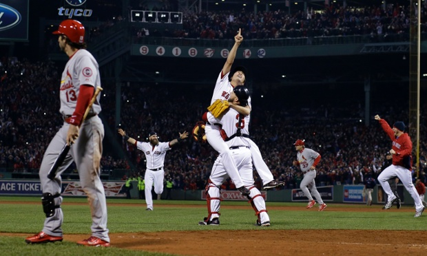 A study of contrasts: Pitcher Koji Uehara and catcher David Ross of the Boston Red Sox celebrate winning the 2013 World Series as Matt Carpenter of the St Louis Cardinals walks off the field.