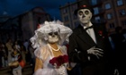 Revellers parade through the streets in traditional costumes at the Day of the Dead festival