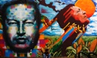A man sits next to a mural depecting the late Venezuelan President Hugo Chavez in downtown Caracas.
