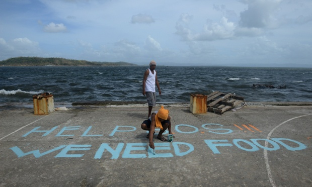 A man paints a message on a baskeball court that reads 'Help SOS We Need Food' at Anibong in Tacloban