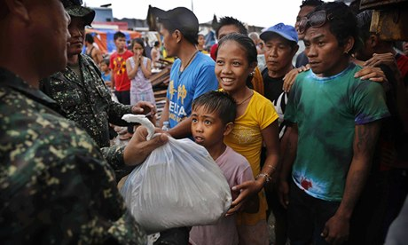 A young Filipino girl and her brother receive food aid at a centre in Tacloban