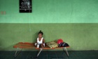 A child sits on a camp bed at a medical centre in Leyte, Philippines.