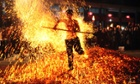 A man walks on burning charcoal as he participates in fire walking in Pan'an county, China
