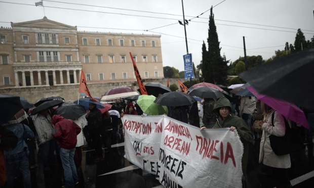Demonstrators march on November 6, 2013 under the rain in front of the parliament in Athens during a 24-hour general strike.