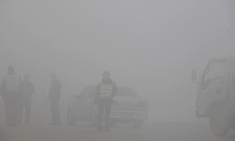 Traffic police barely seen in smog at toll booth, China Jiln province