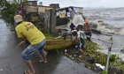 Fishermen in Laguna, Philippines, bring boats ashore as typhoon Haiyan hits