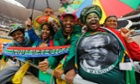 People sing as they arrive for the memorial service of Nelson Mandela at the First National Bank (FNB) Stadium, in Soweto.