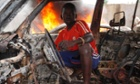 A Christian youth squats inside a burnt out car