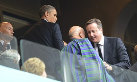 'Move it, baldy! I'm sitting next to Barry' … David Cameron arrnages things at Mandela's funeral.