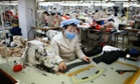 North Korean workers sew items at a factory
