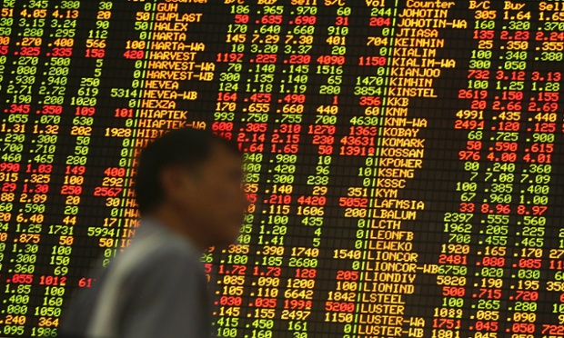 A man walks in front of an electronic board displaying stock prices in Kuala Lumpur, December 19, 2013.