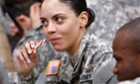 US soldier Mirarie Colon enjoys a candy cane while sitting on the floor with her fellow troops in Oklahoma City while she waits for a flight that will take her home to Chicago.