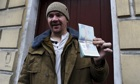 Greenpeace activist Anthony Perrett shows his passport with a Russian transit visa in St Petersburg