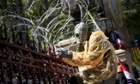 Protester wearing a gas mask cuts through barbed wire in Bangkok.