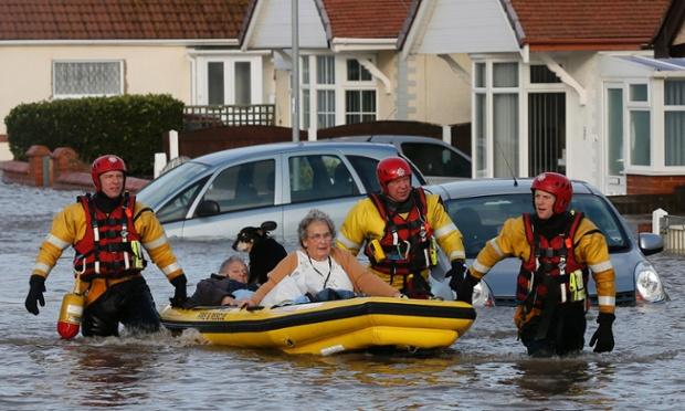 Addetti ai servizi di soccorso di emergenza evacuare i residenti e il loro cane in un gommone in acqua penetrata in una strada residenziale a Rhyl, Galles del nord.