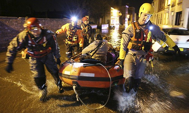 A rescue team pulls a boat with an evacuee in Boston