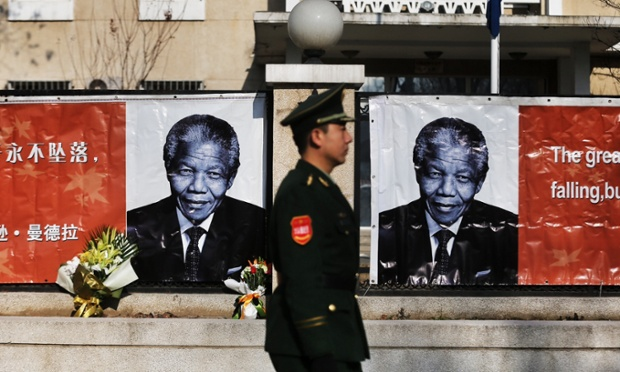 A Chinese security officer walks past images of Nelson Mandela at the Embassy of South Africa in Beijing, China.