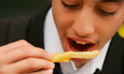 A student eats chips bought from a fast food shop near his school