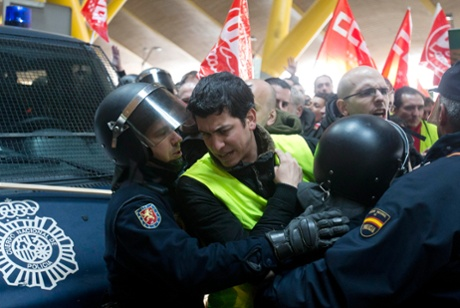 Iberia workers try to break through a police barrier to protest inside Barajas international airport in Madrid, Spain, Monday, Feb. 18, 2013.