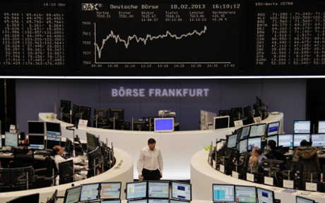 Traders are pictured at their desks in front of the DAX board at the Frankfurt stock exchange February 18, 2013.