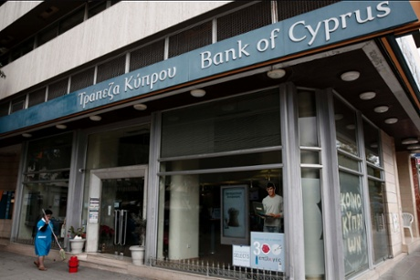 A cleaning worker holds a mop while working in front of a Bank of Cyprus branch in central Nicosia February 18, 2013.