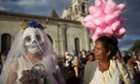 A street vendor looks at a disguised reveler during celebrations marking the International Poetry Festival honoring Nicaraguan poet Ernesto Cardenal in Granada, Nicaragua.