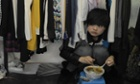 A woman eats her lunch in a shop in a wholesale clothing market in Shanghai. China's manufacturing growth hit a four-month low in February but remained positive, British banking giant HSBC said.