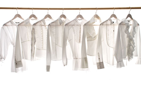 White blouses hanging on a rail
