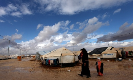 A Syrian refugee walks with her two kids at Za'atari Syrian refugee camp, near the Syrian border in Mafraq, Jordan.