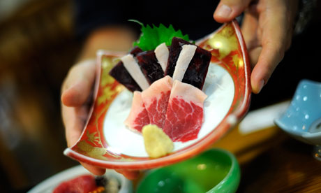 Whale meat sashimi is served with fresh ginger at a hotel in Taiji, Japan