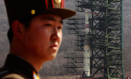A North Korean soldier guards the Unha-3 rocket sitting on a launch pad in Pyongyang.