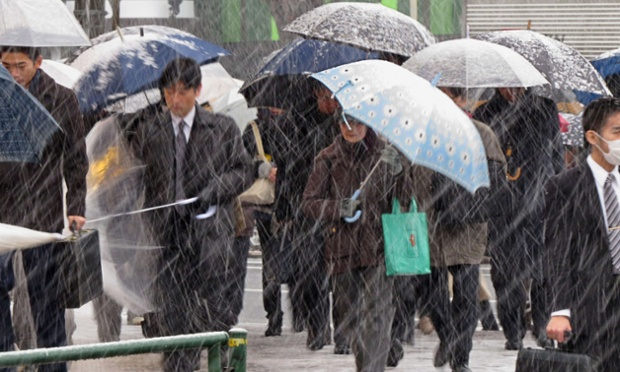 Commuters shelter from the snow under umbrellas whilst on their way to work in Tokyo this morning.