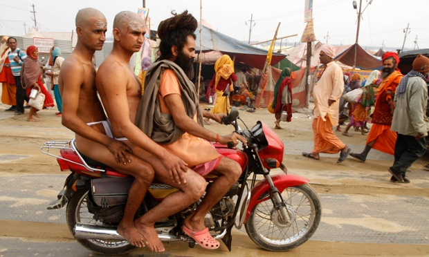 And here two holy men of the Juna Akhara sect  ride on a motorcycle driven by their teacher.