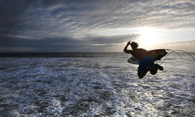 A surfer jumps into the sea from a pier on the beachfront in Durban, South Africa. Many surfers start early in the morning as the sun rises so as to ride a good wave before going to work. Nice.