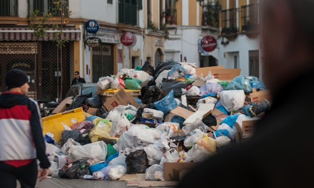 Pedestrians pass a pile of rubbish during the ninth day of the Seville waste disposal workers' strike in Seville, Spain. Workers are striking over demands they take a 5% pay cut and extend their working week to 37.5 hours.