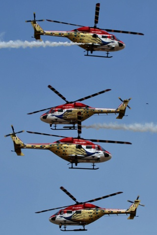 The Indian Air Force Sarang aerobatics team perform in their HAL Dhruv helicopters during Aero India 2013 at the Yelahanka Air Force station in Bangalore.