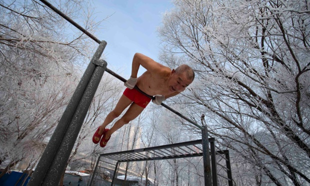 Gao Yinyu, 77, does his morning exercise before swimming in Songhua river in Jilin, China.