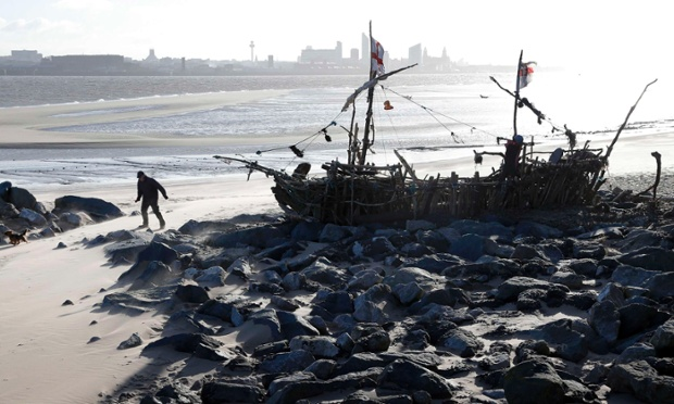 A man walks past a pirate ship made from driftwood and objects washed up on the beach at New Brighton near Liverpool, England this morning.