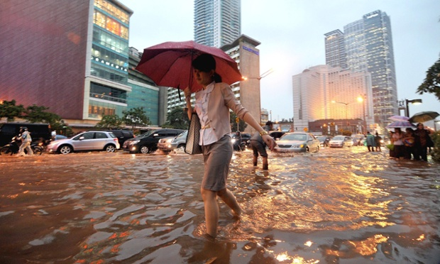 It's even wetter in Indonesia: people walk on the edge of a flooded street in heavy rain in Jakarta.   Jakarta saw another bout of heavy rains with