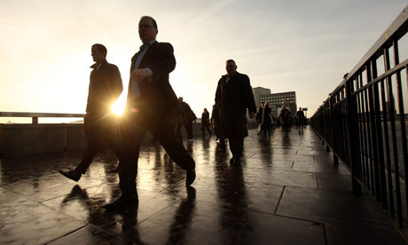 City workers walk across London Bridge on their commute to the financial district