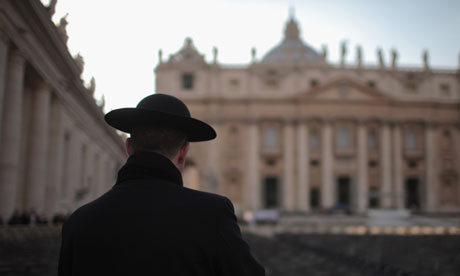 A priest stands next to St Peter's Basilica, Vatican City