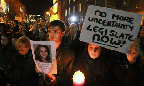 Protestors hold pictures of Savita Halappanavar who died after an Irish hospital refused an abortion