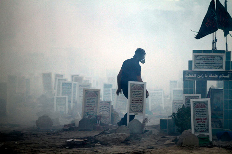 A Bahraini anti-government protester walks through tear gas
