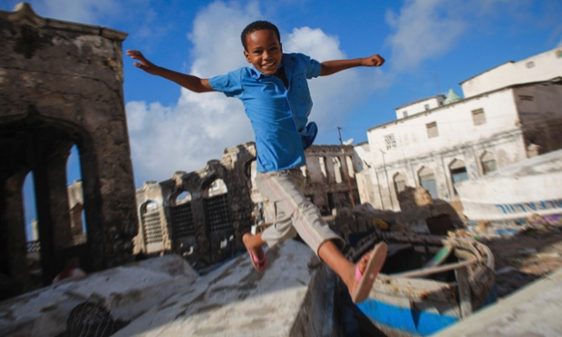 A Somali boy jumps between old fishing boats near Mogadishu's fish market in the Xamar Weyne district of the Somali capital, in this photo taken March 16, 2013 by the African Union-United Nations Information Support Team (AU-UN IST) and released today.